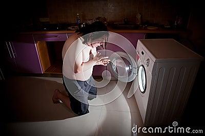 Asian fat man kneel in prayer by washing machine