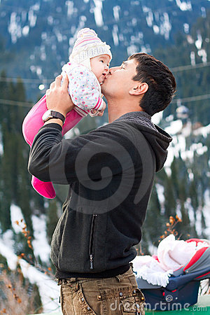 Asian father kissing his baby