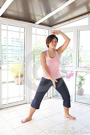 Asian female doing tai-chi exercise.