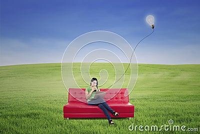 Asian female enjoying tea under lamp outdoor