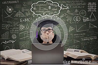 Asian female graduate stressed in class