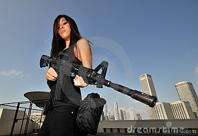 Asian Female holding a mean rifle overlooking city