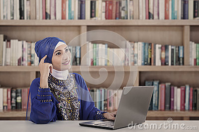 Asian female muslim thinking at library