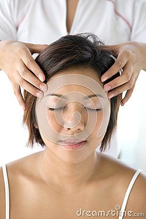 Asian female receiving gentle head massage