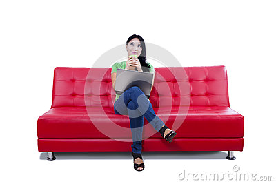 Asian female thinking on red sofa - isolated