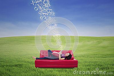 Asian female using touchpad on sofa with flying letters outdoor