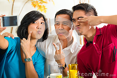 Asian friends taking pictures with mobile phone