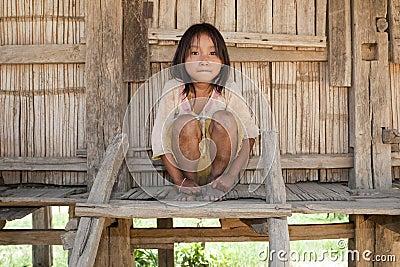 Asian girl Akha before timber house, Laos
