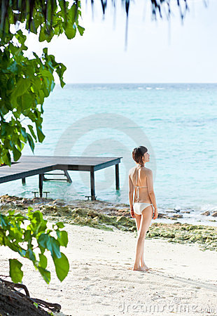 Asian girl in bikini standing on beach