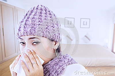 Asian girl blowing nose wearing beany in winter