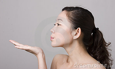 An Asian girl blowing something on her hand