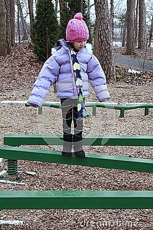 Asian girl bundled for cold walking on beam