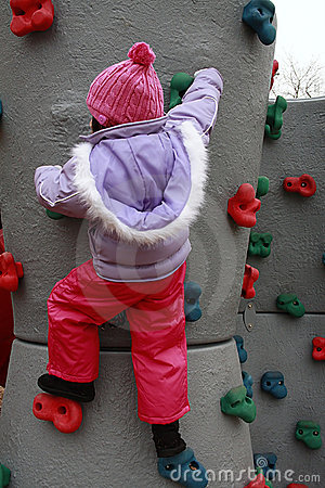 Asian girl bundled for winter climbing rock wall