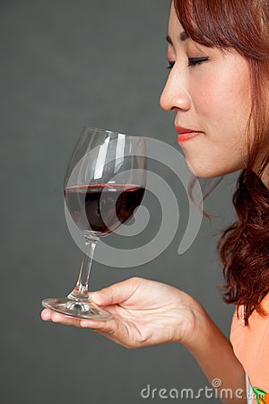 Asian girl close her eyes and smell aroma of red wine