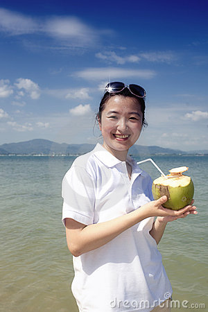 Asian girl drinking coconut on the beach