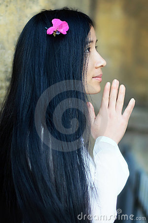 Asian girl with flower in her hairs praying