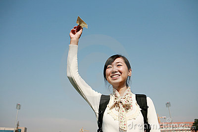 Asian girl holding paper aircraft