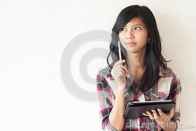 Asian girl holding a tablet pc and thinking about some idea