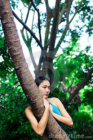 Asian girl hugging tree
