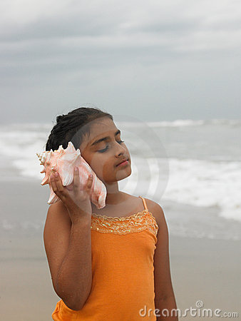 Asian girl listening to the conch
