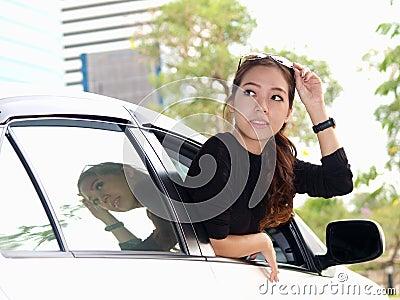 Asian girl looking at back of car