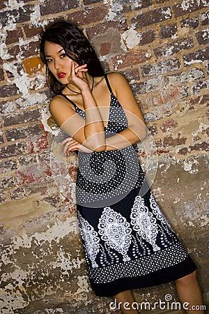 Asian girl near brick wall