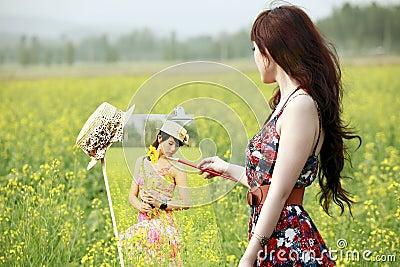 Asian girl painting in rape field