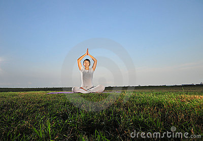 Asian Girl performing Yoga on grass/ park