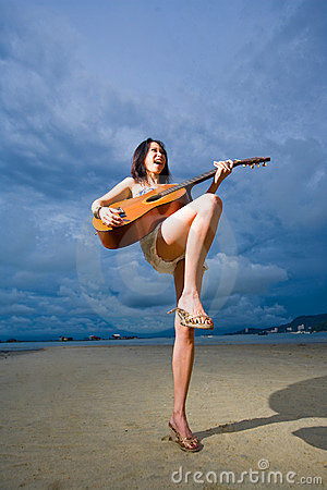 Asian girl playing guitar at the beach