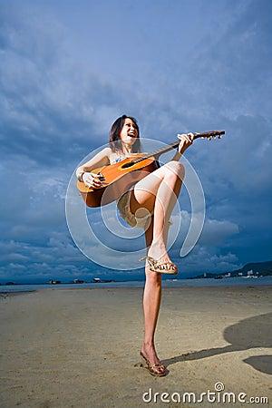 Asian girl playing guitar at the beach