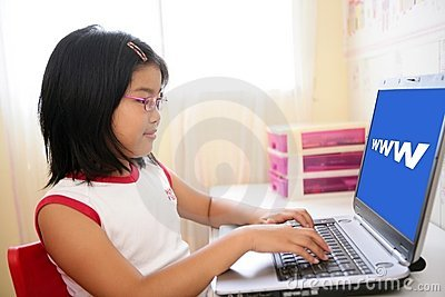 Asian girl playing with laptop computer on table