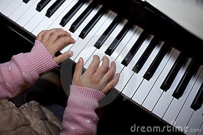 Asian girl playing the piano at home
