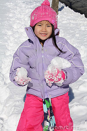 Asian girl playing in snow with chunks