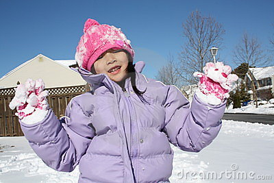 Asian girl playing in snow with gloves up