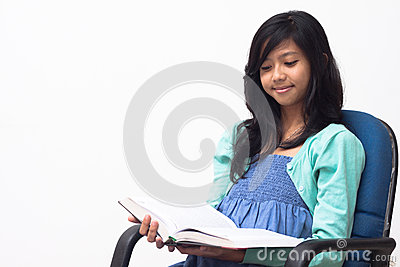 Asian girl sitting on the chair and read her book