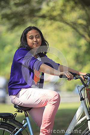 Asian girl riding bicycle in public park with green blurry background use as for multipurpose in healthy life style topic