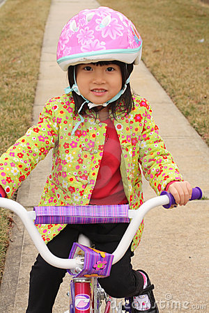 Asian girl riding on bike with helmet