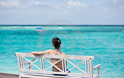 Asian girl sitting in chair watching the sea