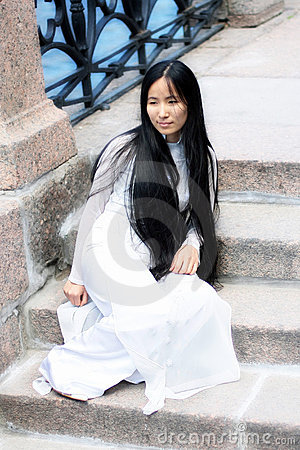 Asian girl sitting on stone embankment