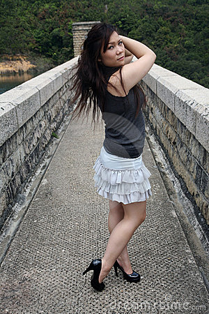 Asian girl standing alone outdoors
