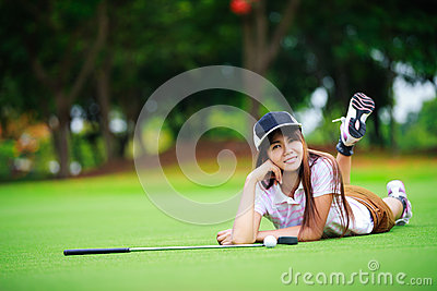 Asian golfer laying on the green grass
