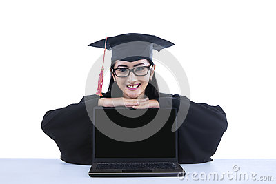 Asian graduate with blank screen laptop