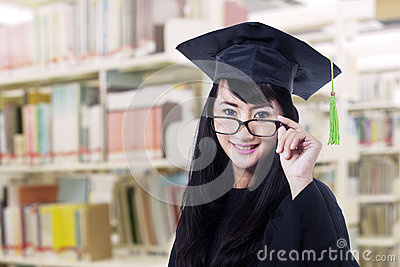 Asian graduate in graduation gown pose at library