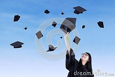 Asian graduate throw graduation cap in air