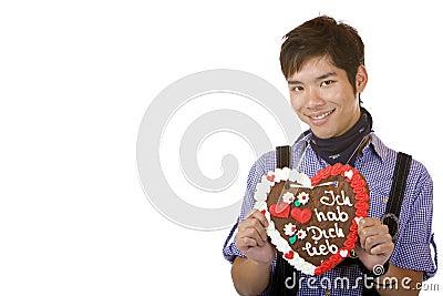 Asian holds Oktoberfest gingerbread heart