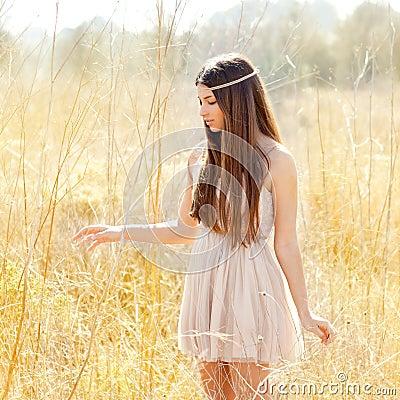 Asian indian woman walking in golden dried field