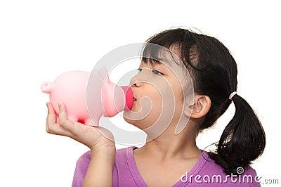 Asian kid kissing piggy bank