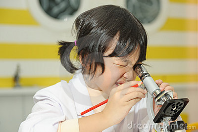 Asian kid looking into microscope