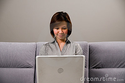 Asian lady in business attire, using a computer