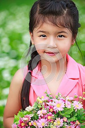 Asian little girl with flower in field of flowers